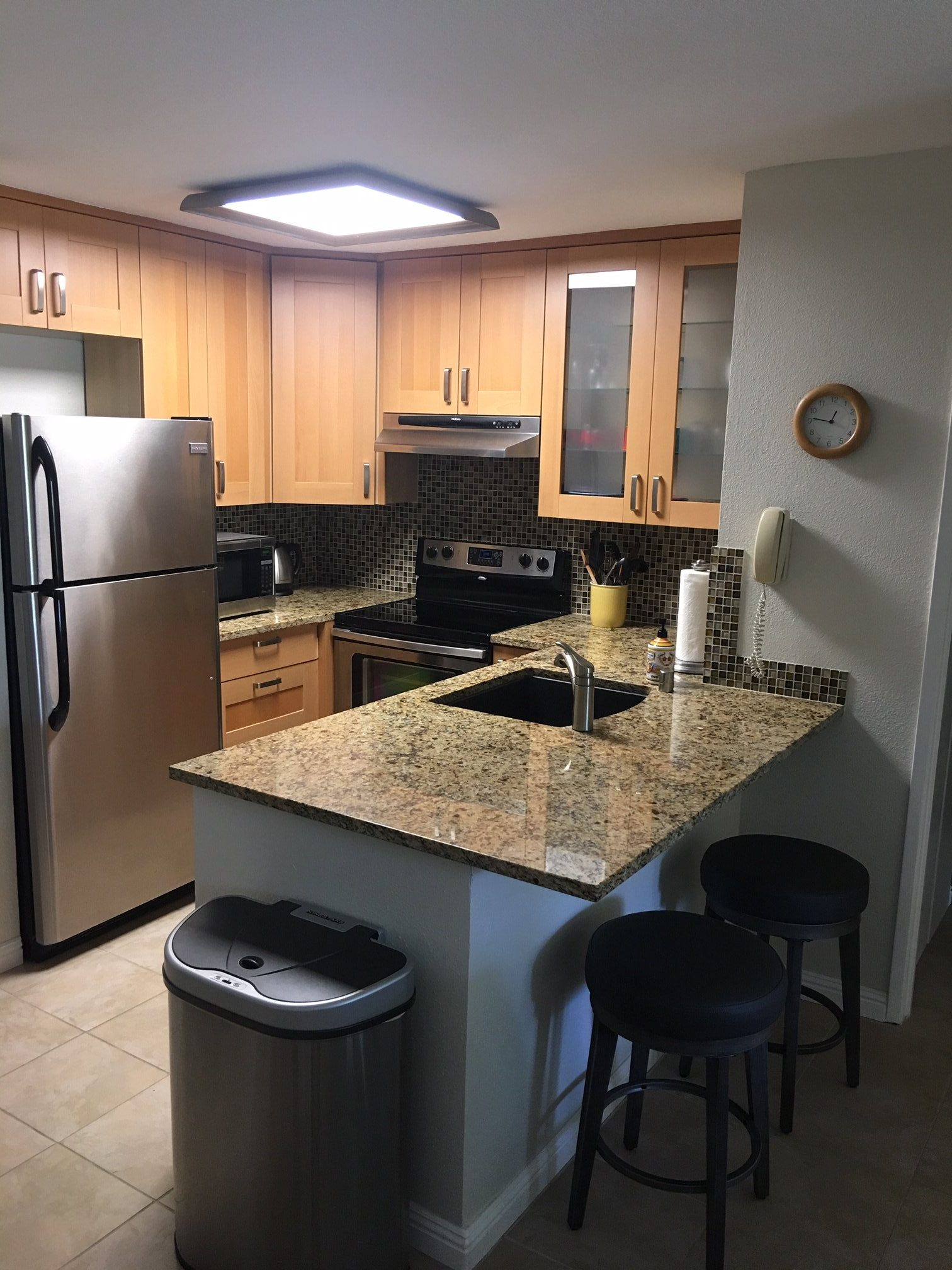 Unit F-106 Kitchen with stainless steel appliances, and breakfast bar with 2 stools