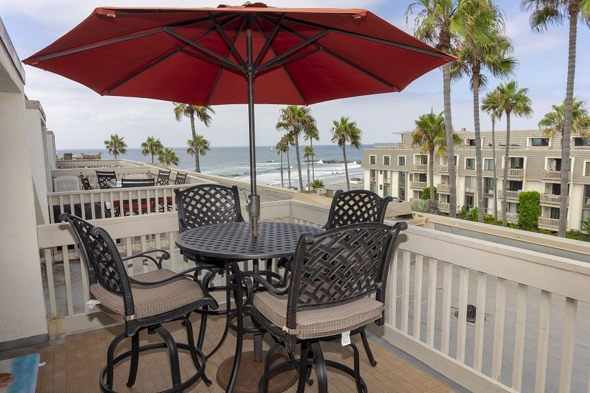 large patio with 4 chairs and a table with red umbrella overlooking the pacific ocean